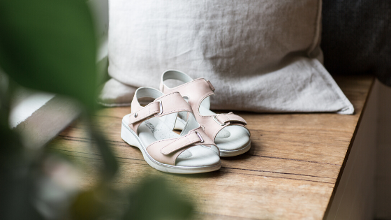 A pair of taupe Scream sandals laying on wooden floorboards